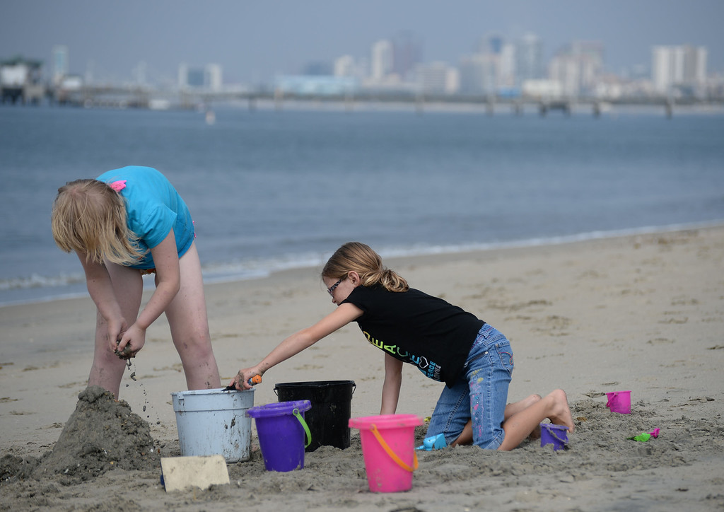 . Children had a chance to hone their sand castle building skills in a sand castle camp Monday at Granada Beach in Belmont Shore. Shelby Randall, left, and Kayleen Lindberg, right, work on their creation as the sun begins to emerge from clouds to reveal the city\'s skyline. 20130805 Photo by Steve McCrank / Staff Photographer
