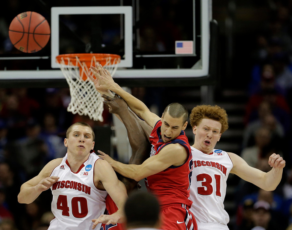 . Mississippi guard Marshall Henderson, center, battles Wisconsin forward/center Jared Berggren (40) and forward Mike Bruesewitz (31) for a rebound during the second half of a second-round game of the NCAA college basketball tournament Friday, March 22, 2013, in Kansas City, Mo. (AP Photo/Charlie Riedel)