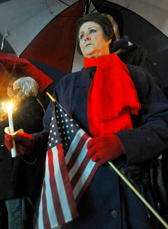 . A somber woman holds an American flag and candle in the rain during a candlelight vigil in honor of fallen San Bernardino County Sheriff\'s Detective Jeremiah MacKay at the Yucaipa Community Center in Yucaipa, Calif. on Tuesday, Feb. 19, 2013. MacKay was killed by fugitive ex-cop Christopher Dorner on Feb. 12 during a fiery shootout in which Dorner barricaded himself in a cabin near Big Bear. (Rachel Luna / Staff Photographer)