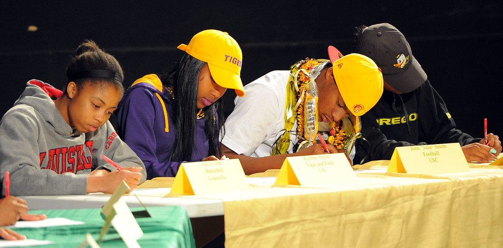 """. From left, Arica Carter (Luisville basketball), Kymber Payne (LSU track), John \""""JuJu\"""" Smith (USC football) and Ariana Washington (Oregon track) sign their national letters of intent during a ceremony in Long Beach, CA on Wednesday, February 5, 2014. 18 students athletes at Long Beach Poly signed their national letters of intent to play athletics at 4-year universities. (Photo by Scott Varley, Daily Breeze)"""
