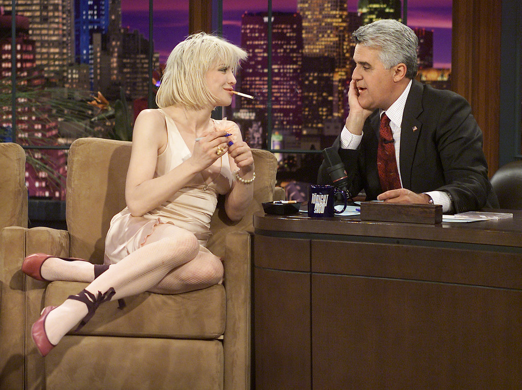 """. Rocker Courtney Love talks with host Jay Leno while making her first appearance on \""""The Tonight Show with Jay Leno,\"""" Thursday, April 15, 2004, in Burbank, Calif. During the show, Love discussed her recent legal troubles, her image and the tabloids before performing with her band. A judge Thursday ordered Love to stand trial on felony drug charges after hearing testimony alleging that she gave police officers a baggie full of pills. (AP Photo/NBC, Paul Drinkwater)"""