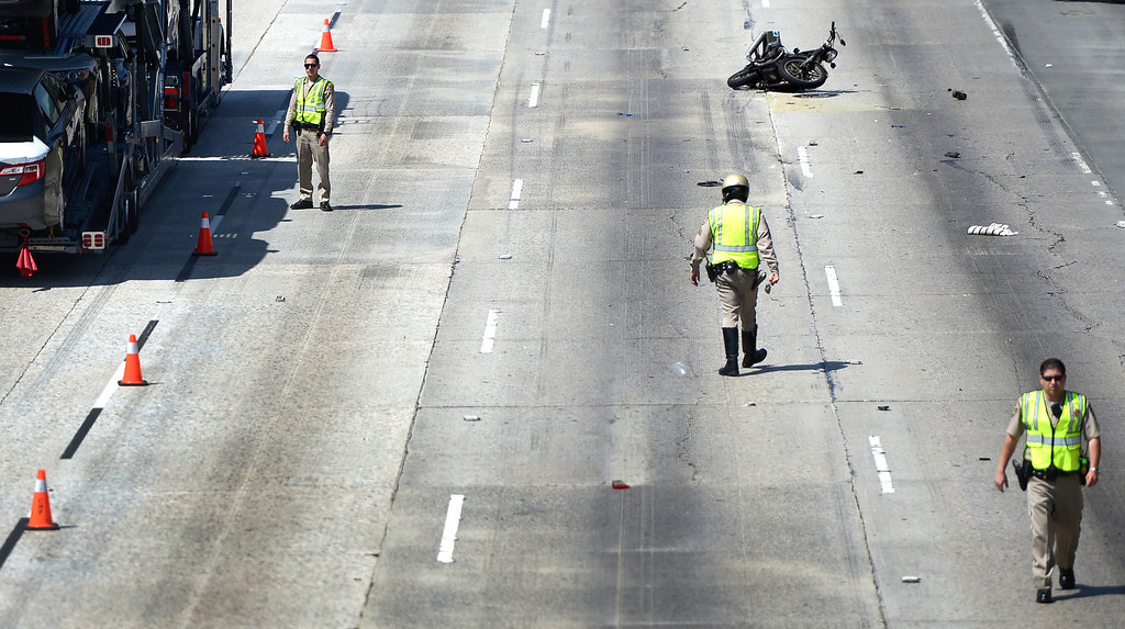 Description of . California Highway Patrol officers investigate a fatal motorcycle crash on the westbound 60 Freeway east of Hacienda Boulevard in Hacienda Heights Tuesday, March 26, 2013.(SGVN/Staff Photo by Sarah Reingewirtz)