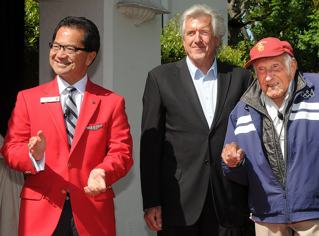 Description of . Tournament President Richard L. Chinen, left, Luke Zamperini son of Louis Zamperini, right, listening to USC band  playing USC music after Louis Zamperini , who attended USC, was selected 2015 Tournament of Roses Grand Marshal. Olympian and World War II prisoner of war, Louis Zamperini, a true American Hero who survived excessive hardships. (Photo by Walt Mancini/Pasadena Star-News)