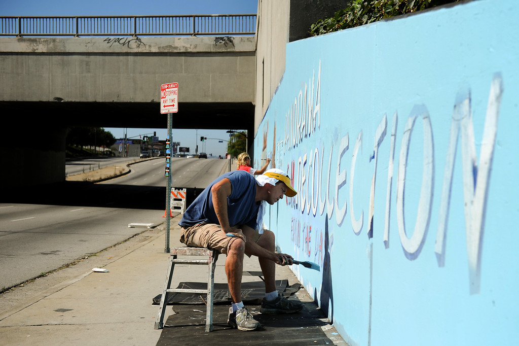 ". Jeff Lingle paints during restoration of the mural ""Panorama: G.M. Recollections from the Past,\"" on Van Nuys Boulevard in Panorama City, Thursday, June 20, 2013. The original mural was painted by Alfredo Diaz Flores in 1998 and pays homage to the General Motors plant that used to be near the mural site. (Michael Owen Baker/Staff Photographer)"