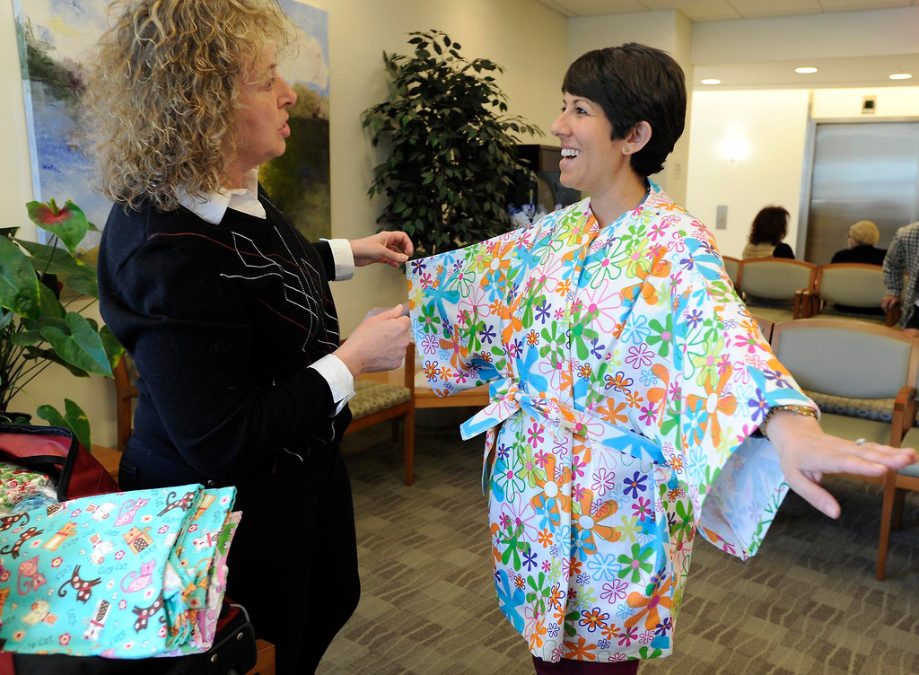 . (l-r) Brenda Jones looks at the Hug Wrap she gave to patient Liz Barnett. Jones created her own open-in-the-front wrap when she was undergoing treatment for breast cancer, crafting an option to the hospital gown, utilizing soft and colorful flannel fabrics. Fellow patients loved them and her nonprofit Hug Wraps was born. Jones visited Providence Saint Joseph Medical Center�s Roy and Patricia Disney Family Cancer Center and gave patients free wraps. Burbank, CA 2/22/2013(John McCoy/Staff Photographer)
