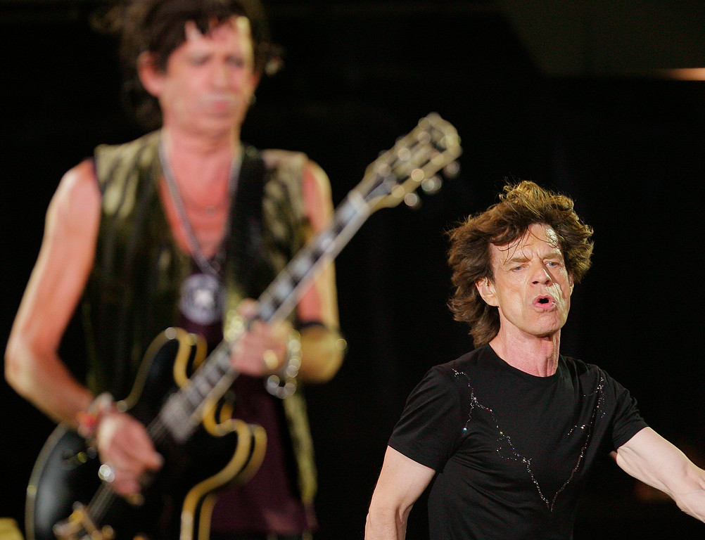 ". Mick Jagger, right, runs behind Keith Richards, left, during their performance at a concert of the Rolling Stones ""A Bigger Bang\"" European Tour, in Bucharest, Romania, Tuesday July 17, 2007. (AP Photo/Vadim Ghirda)"
