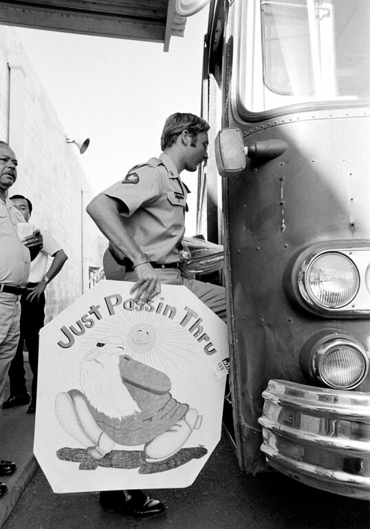 . Spc 4 Scott McPherson of California carries an appropriate sign he made during his Vietnam tour of duty as he boards a bus in Saigon, Jan. 30, 1973, which will take him to the airport for a flight back to the United States.  Under terms of the ceasefire agreement, all U.S. troops must be withdrawn from Vietnam within 60 days after signing of the pact.  (AP Photo)