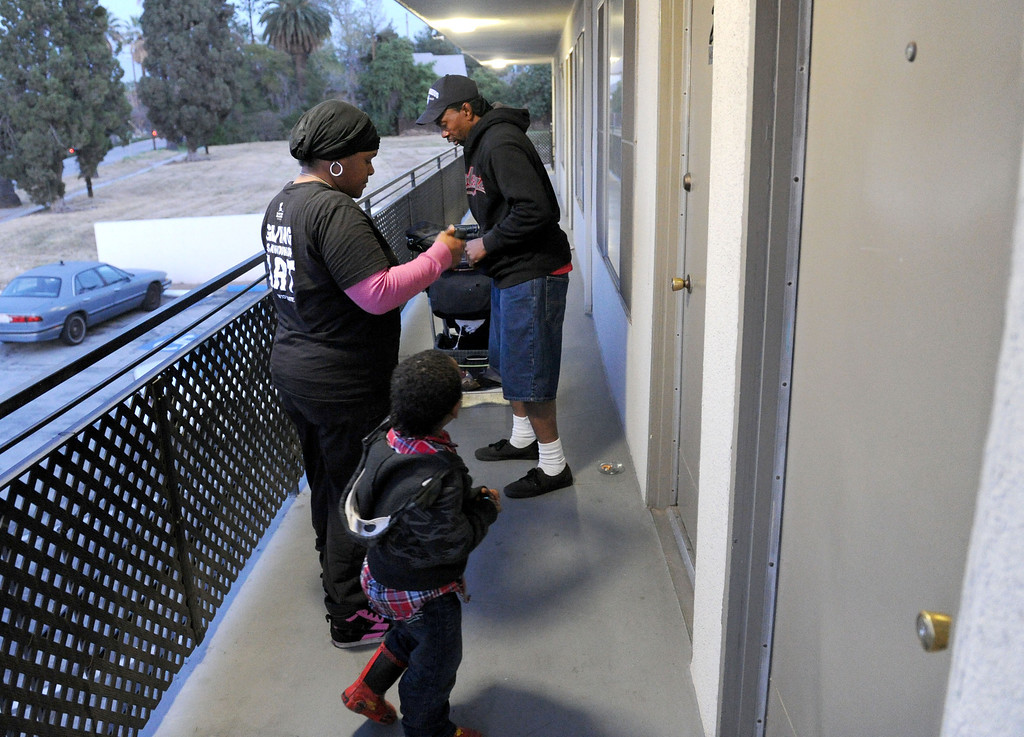 Description of . (John Valenzuela/Staff Photographer)  Danielle Parks, Curtis Wagner and son Curtis Jr.of Redlands, get back to their motel room where they've been living for the past three week.  After getting evicted from their home in San Bernardino in December, Parks and Wagner have had to struggle to make ends meet, getting help from family and handouts from the community, along with panhandling to earn money for their motel room.