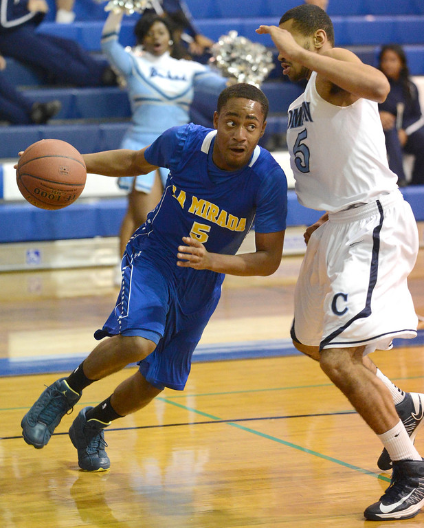 Description of . La Mirada's Tyler Payne (5) drives against Compton's Kevlin Swint (5)in a first round CIF Division 3AAA basketball game Wednesday night in Compton. 20130213 Photo by Steve McCrank / Staff Photographer