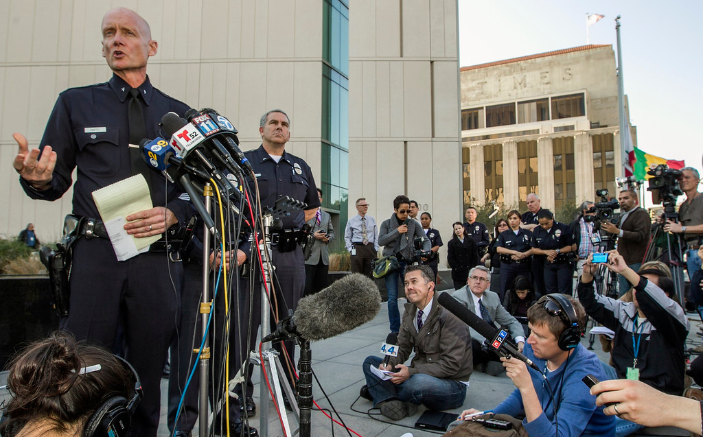 Description of . Los Angeles Police Commander Andrew Smith, left, briefs the media about the shootout scene in Big Bear that allegedly involves triple-murder suspect Christopher Jordan Dorner, during a news conference in front of the Police Administration Building in Los Angeles Tuesday, Feb. 12, 2013. (AP Photo/Damian Dovarganes)