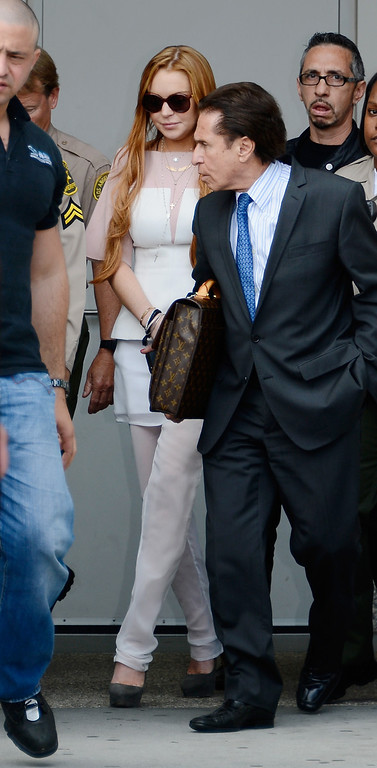 . LOS ANGELES, CA - MARCH 18:  Lindsay Lohan (C) and her lawyer Mark Heller leave after Lohan\'s trial for allegedly lying to police after a car crash, reckless driving and violating her probation for a 2011 jewelry theft conviction at Airport Branch Courthouse of Los Angeles Superior Court March 18, 2013 in Los Angeles, California. Lohan pleaded no contest to two counts in a plea deal and sentenced to 90 days in locked rehab, 30 days community labor and 18 months psychotherapy.  (Photo by Kevork Djansezian/Getty Images)