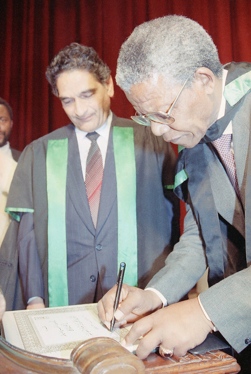 . Nelson Mandela, South African leader Anti-Apartheid leader, signs a document certifying his acceptance of an honorary doctorate in philosophy from the University of Cairo on May 20, 1990 at Cairo, Egypt.    At left is the presidnt of Cairo University Dr. Maamoun Salama.  (AP Photo)