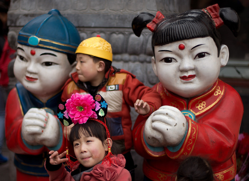 . Children wearing traditional Chinese hats pose with a pair of statues on display at a shopping district in Beijing Thursday, Feb. 14, 2013. (AP Photo/Andy Wong)
