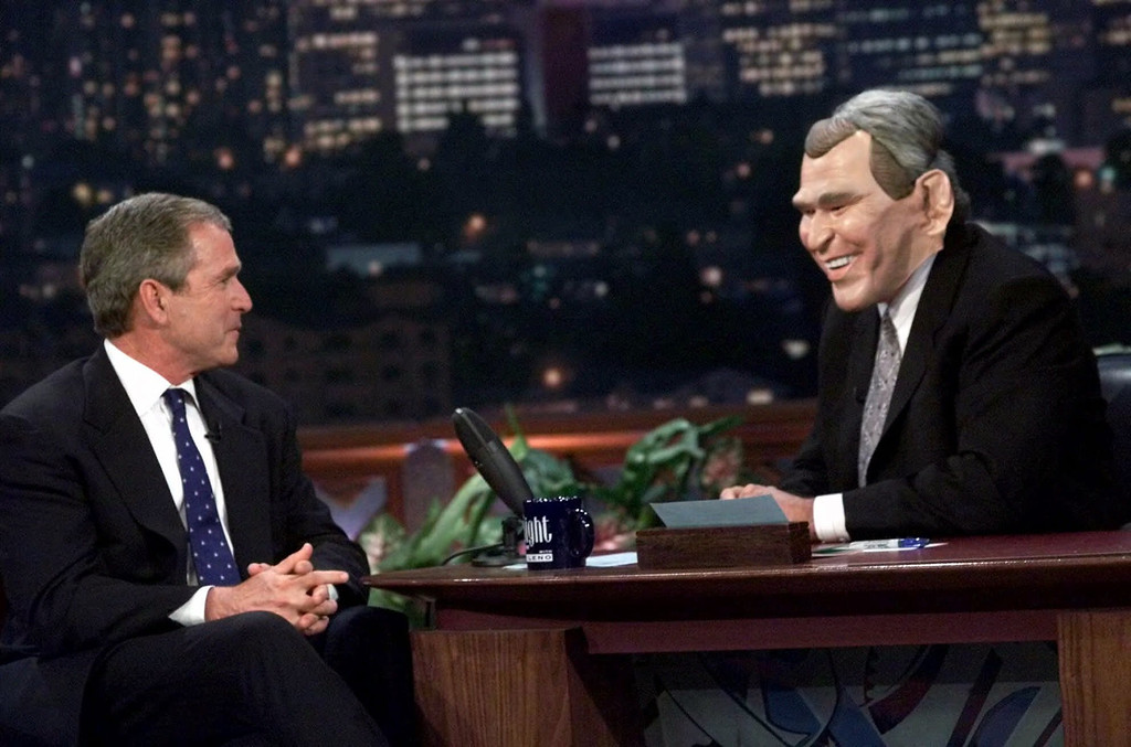 ". Talk show host Jay Leno, right, wears a Texas Gov. George W. Bush mask while interviewing the Republican presidential candidate during the taping of ""The Tonight Show with Jay Leno,\"" Monday, Oct. 30, 2000, in Burbank, Calif. (AP Photo/Eric Gay)"