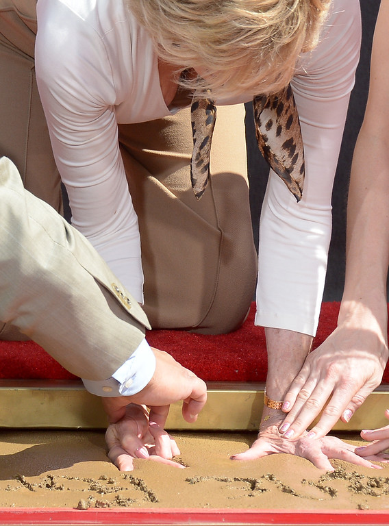 . Jane Fonda prints her hands in wet cement during her Handprint/Footprint Ceremony during the 2013 TCM Classic Film Festival at TCL Chinese Theatre on April 27, 2013 in Los Angeles. Fonda is an American actress, writer, political activist, former fashion model, and fitness guru. She rose to fame in the 1960s with films such as Barbarella and Cat Ballou. She has won two Academy Awards, an Emmy Award, three Golden Globes and received several other movie awards and nominations during more than 50 years as an actress. After 15 years of retirement, she returned to film in 2005 with Monster-in-Law, followed by Georgia Rule two years later. She also produced and starred in over 20 exercise videos released between 1982 and 1995, and once again in 2010.  (JOE KLAMAR/AFP/Getty Images)