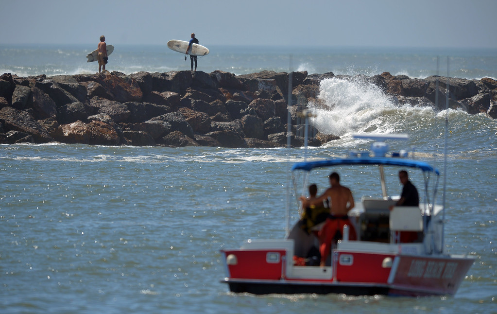 . A LBFD boat crew keeps an eye on the channel leading from Alamitos Bay to the ocean as surfers on the Seal Beach side head out on the breakwall to go surfing in Long Beach, CA on Wednesday, August 27, 2014. With city crews constantly building a sand berm, the water was held back from the homes and streets during the morning high tide. (Photo by Scott Varley, Daily Breeze)