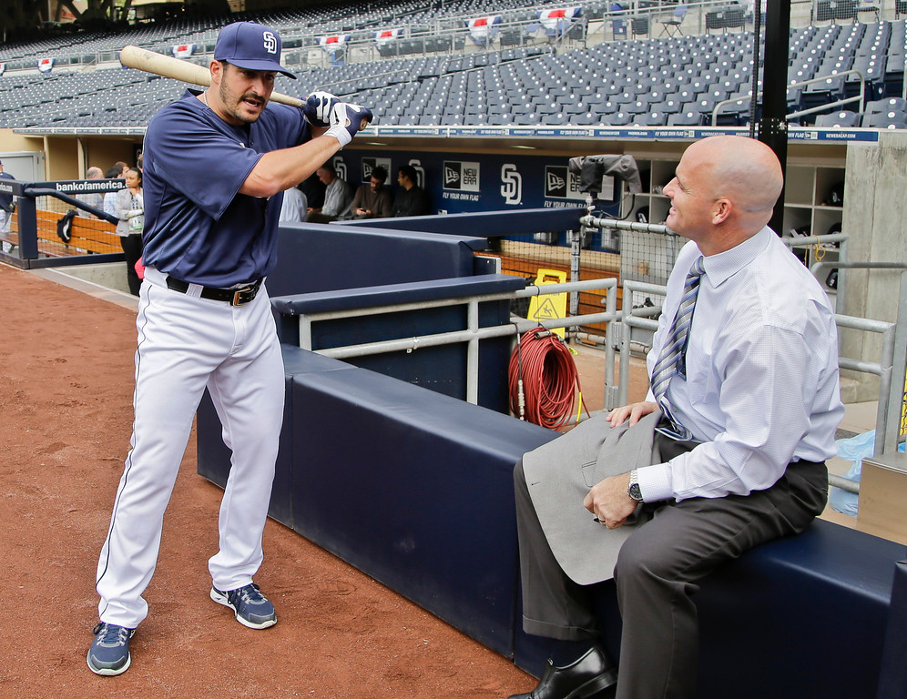 . San Diego Padres pitcher Jason Marquis, talks hitting with former player and current broadcaster Mark Sweeney,  prior to his start against the Los Angeles Dodgers in a baseball game in San Diego, Thursday, April 11, 2013. (AP Photo/Lenny Ignelzi)