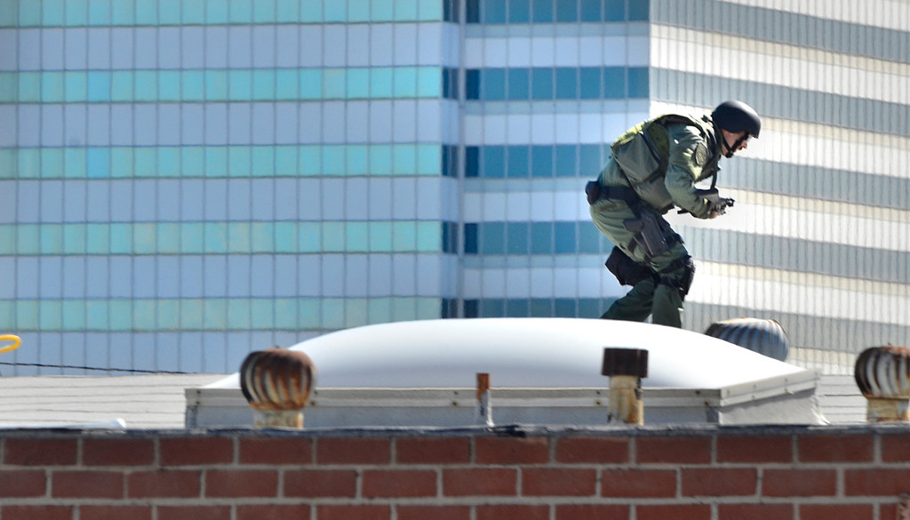 . SWAT team member scurries across a rooftop in El Segundo during a hostage situation at the Popcornopolis offices near El Segundo Blvd. Armed female employee took another employeee hostage which ended peacefully after about 4 hours. Photo by Brad Graverson 4-16-13