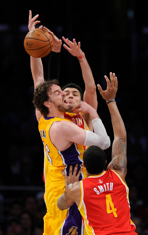 . Lakers#16 Pau Gasol is fouled by Rockets#10 Carlos Delfino as Rockets#4 Greg Smith looks to grab the ball in the first quarter. The Lakers faced the Houston Rockets in the final home game of the year at Staples Center in Los Angeles, CA 4/17/2013(John McCoy/Staff PhotographerThe Lakers faced the Houston Rockets in the final home game of the year at Staples Center in Los Angeles, CA 4/17/2013(John McCoy/Staff Photographer