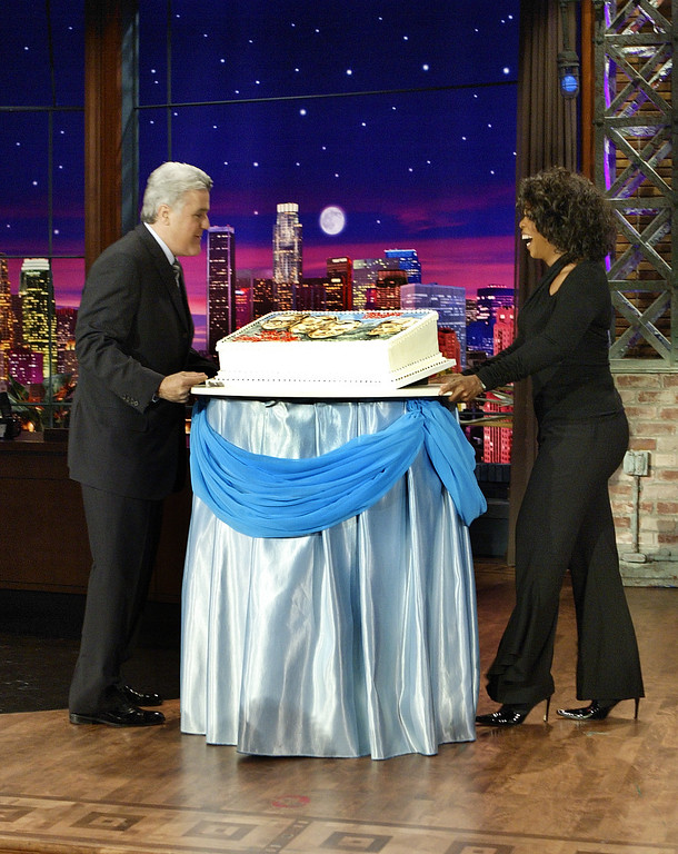 """. \""""Tonight\"""" show host Jay Leno, left, and Oprah Winfrey celebrate the 50th anniversary of the \""""Tonight\"""" show with a cake commemorating its hosts from past and present, Steve Allen, Jack Paar, Johnny Carson and Jay Leno, on Monday, Sept. 27, 2004, in Burbank, Calif. NBC chose the 50th anniversary of the ``Tonight\'\' show on Monday to announce that Leno will be succeeded by ``Late Night\'\' host Conan O\'Brien in five years, or thousands of jokes from now. (AP Photo/NBC, Paul Drinkwater)"""