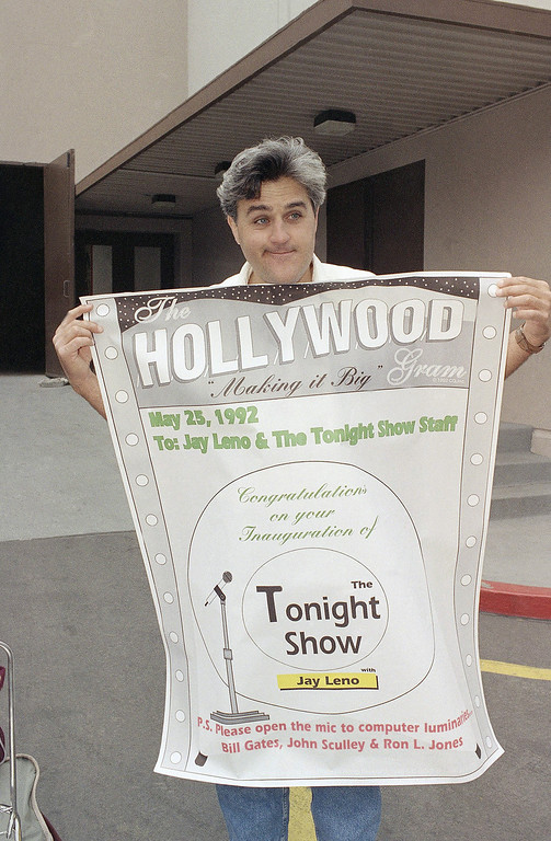". Jay Leno holds up a sign congratulating him on the inauguration of ""The Tonight Show with Jay Leno,\"" outside the NBC Studios in Burbank, Calif., May 25, 1992. A fan from Palo Alto, Calif., made the sign and presented it to Leno while waiting in line to see the first show Monday night. Leno took over as host of the show after Johnny Carson retired. (AP Photo/Kevork Djansezian)"
