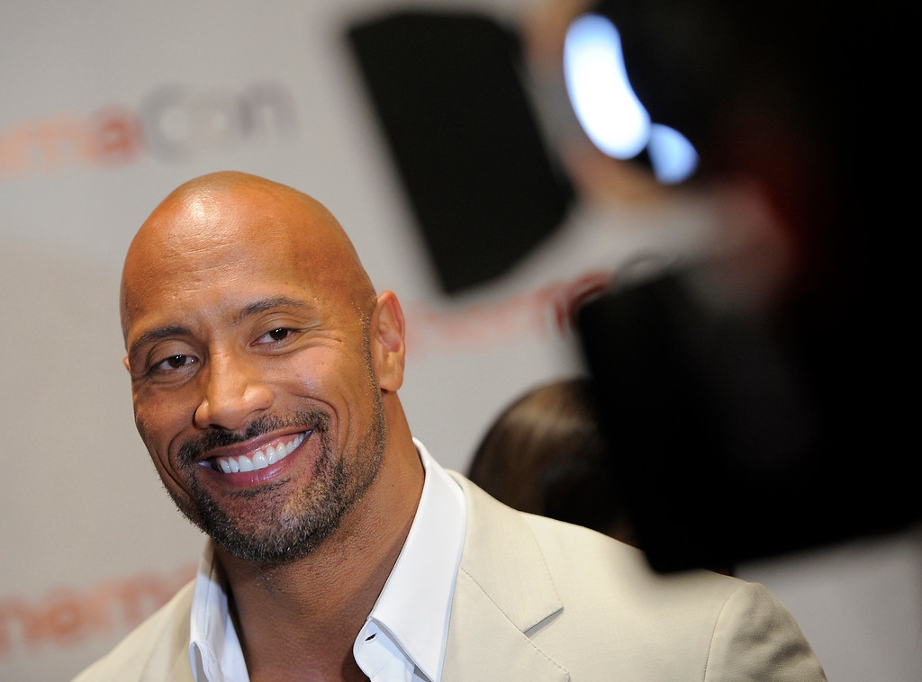 ". Dwayne Johnson, a cast member in the upcoming film ""G.I. Joe: Retaliation,\"" smiles during an interview on the opening night of CinemaCon 2012, the official convention of the National Association of Theater Owners, Monday, April 23, 2012. (AP Photo/Chris Pizzello)"