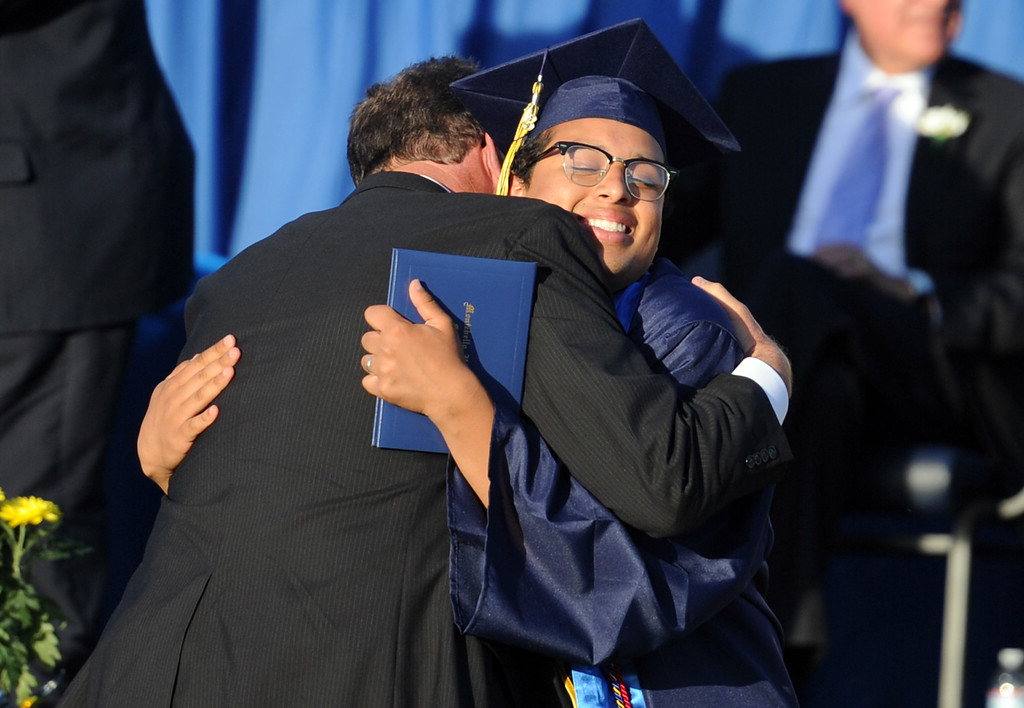 Description of . Graduate Oscar Alvarado hugs principal Jeffrey Schwartz during the Montebello High School commencement at Montebello High School on Thursday, June 20, 2013 in Montebello, Calif.  (Keith Birmingham/Pasadena Star-News)