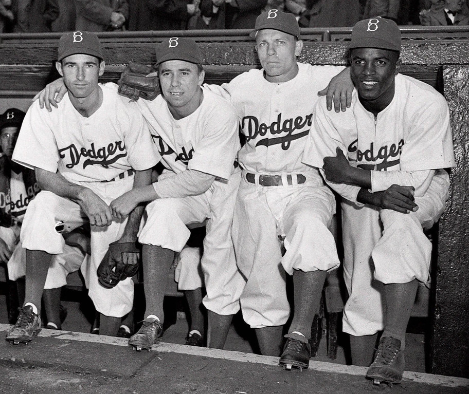"Description of . FILE - In this April 15, 1947 file photo,  from left, Brooklyn Dodgers baseball players John Jorgensen, Pee Wee Reese, Ed Stanky and Jackie Robinson pose at Ebbets Field in New York. Kansas City\'s Negro Leagues Baseball Museum is hosting an advance screening of an upcoming movie about Robinson, who broke major league baseball\'s color barrier. Thomas Butch of the financial firm Waddell and Reed announced Wednesday, March 20, 2013 that actors Harrison Ford and Andre Holland will be among those appearing at an April 11 screening of ""42.\""   (AP Photo, File)"