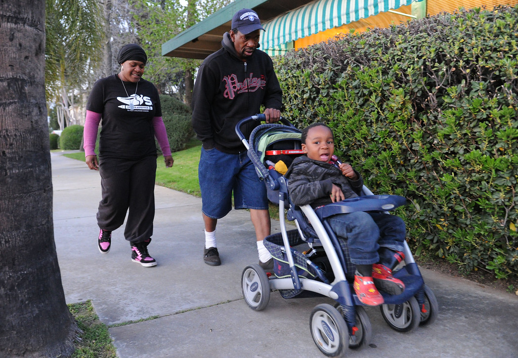 . (John Valenzuela/Staff Photographer)  Danielle Parks and Curtis Wagner of Redlands walk with there son Curtis Jr., back to their motel where they\'ve been living for the past three week.  After getting evicted from their home in San Bernardino in December, Parks and Wagner have had to struggle to make ends meet, getting help from family and handouts from the community, along with panhandling to earn money for their motel room.