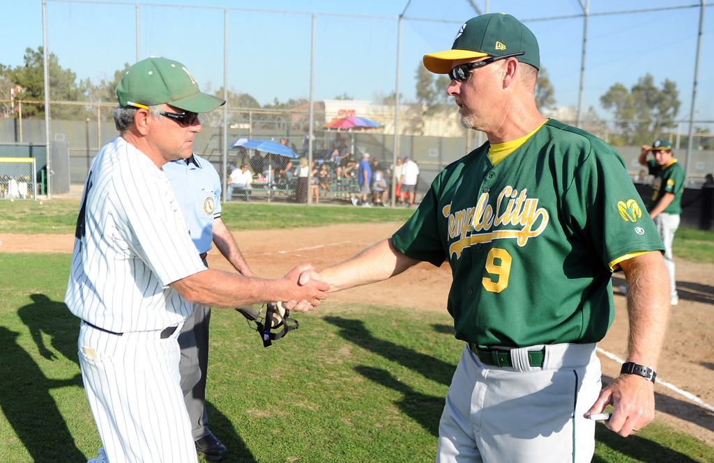 . Temple City head coach Barry Bacon (9) congratulates Nogales coach John Romano after getting his 600th victory with a 2-0 win over Temple City during a prep baseball game at Nogales High School on Tuesday, March 12, 2013 in West Covina, Calif. Nogales won 2-0.