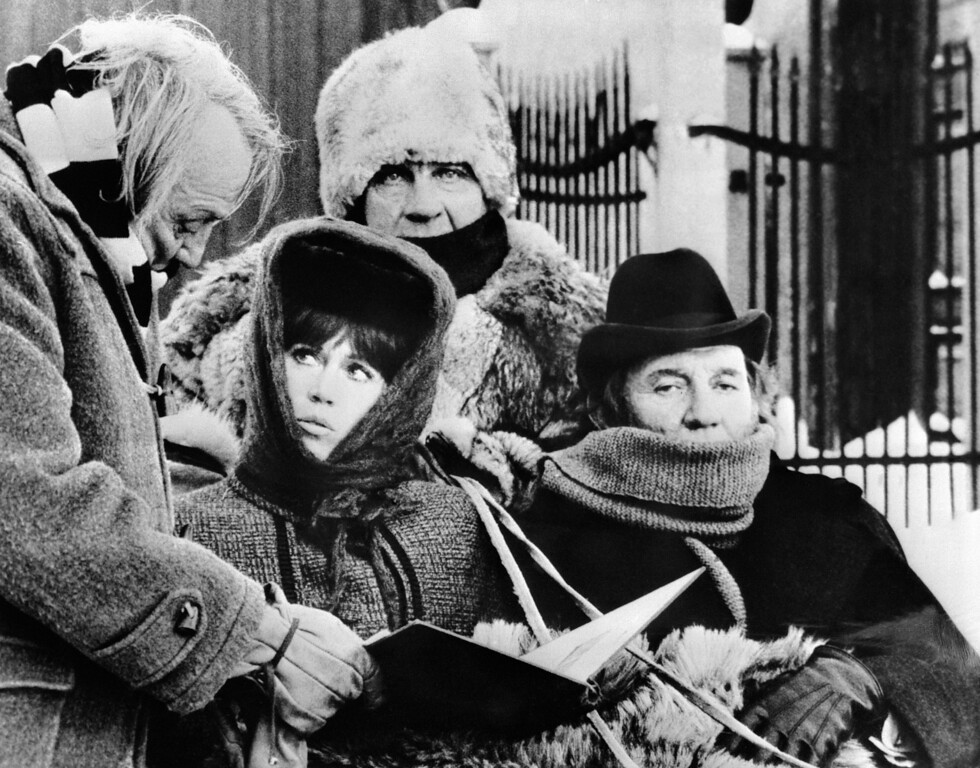 ". US actress Jane Fonda (2nd L) talks with American film director Joseph Losey (L), next to British actor Trevor Howard (R) during the shooting of the film ""A Doll\'s House\"" in December 1972 in Norway.  (AFP/Getty Images)"