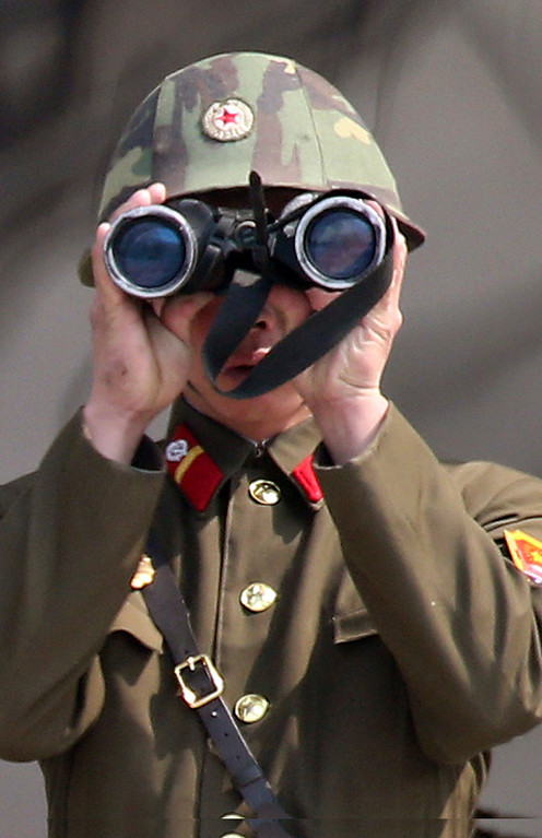". A North Korean soldier uses a pair of binoculars to watch the South Korean side at the border village of Panmunjom in the demilitarized zone (DMZ) in South Korea Thursday, April 4, 2013. South Korea\'s defense minister said Thursday North Korea has moved a missile with ""considerable range\"" to its east coast, but said it is not capable of hitting the United States. (AP Photo/Yonhap, Lee Jong-hoon)  KOREA OUT"