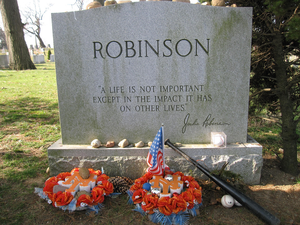 Description of . This April 9, 2013 photo shows Jackie Robinson�s gravesite, where fans still leave tributes to the man who integrated Major League Baseball when he joined the Brooklyn Dodgers in 1947. A new movie, �42,� about Robinson�s life is bringing his inspiring story to a new generation. Fans young and old can find a number of places in Brooklyn connected to Robinson, including his burial site in Cypress Hills Cemetery, which straddles the border of Brooklyn and Queens and is reachable via the Jackie Robinson Parkway. (AP Photo/Beth J. Harpaz)