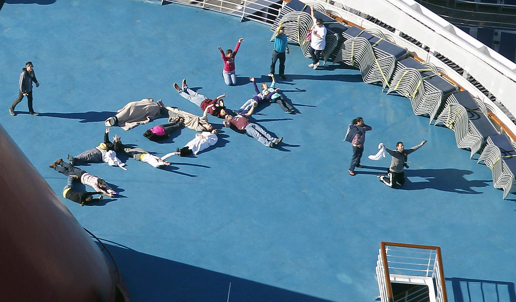 ". Passengers spell out the word ""HELP\"" aboard the disabled Carnival Lines cruise ship Triumph as it is towed to harbor off Mobile Bay, Ala., Thursday, Feb. 14, 2013. The ship with more than 4,200 passengers and crew members has been idled for nearly a week in the Gulf of Mexico following an engine room fire. (AP Photo/Gerald Herbert)"