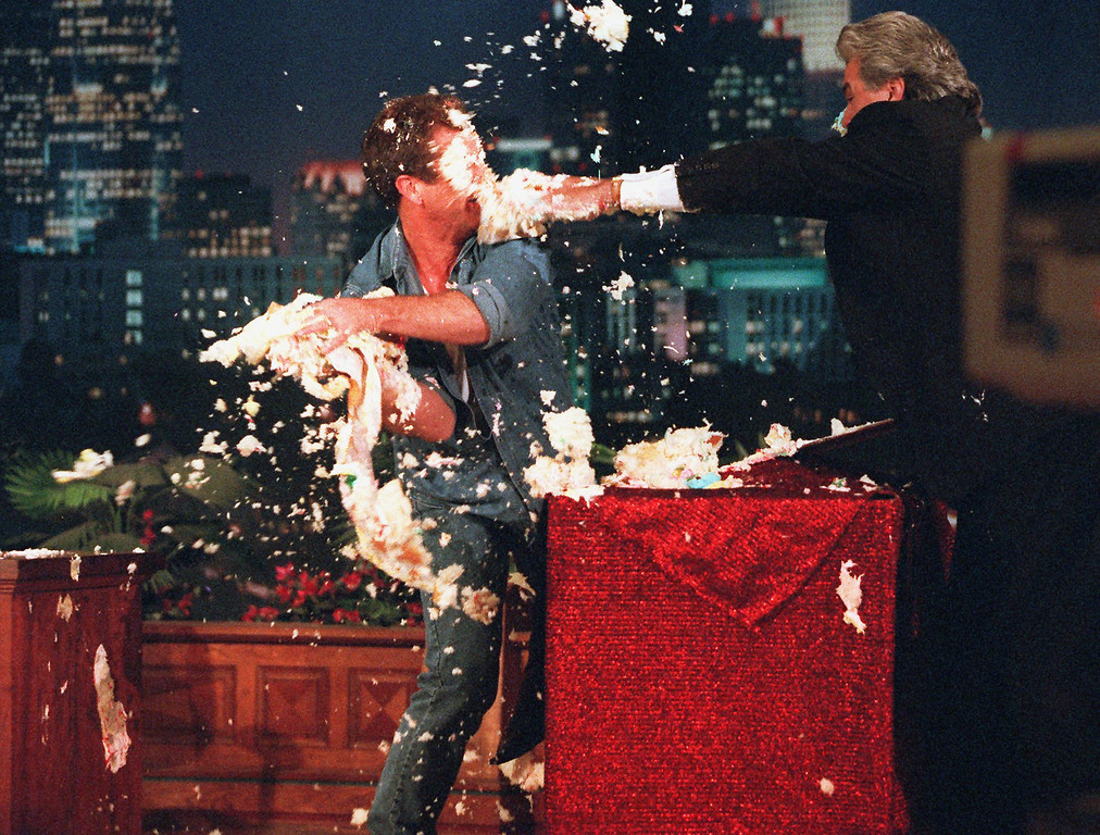 ". Jay Leno, host of ""The Tonight Show,\"" right, is hit with his anniversary cake by actor/director Mel Gibson, left, during his fifth year anniversary show at the Burbank, Calif., studio Thursday, May 22, 1997. Leno is celebrating his fifth year as host of \""The Tonight Show,\"" succeeding Johnny Carson. (AP Photo/Damian Dovarganes)"