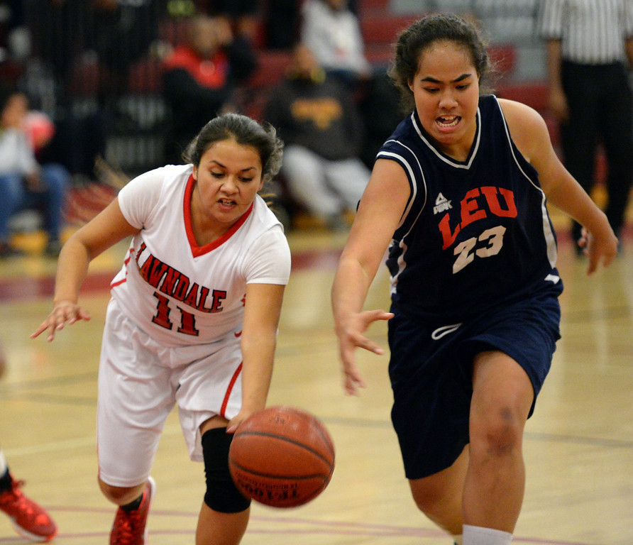 . Lawndale\'s Roxanne Gorostieta (11) chases a loose ball against Leuzinger\'s Taiana Puloka (23) in a girls basketball game at Lawndale High Tuesday, December 10, 2013, in Lawndale, CA.  Photo by Steve McCrank/DailyBreeze