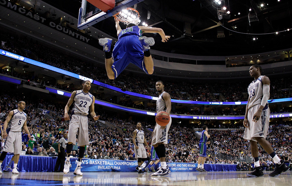 . Florida Gulf Coast\'s Chase Fieler (20) hangs from the rim after a dunk as Georgetown\'s Markel Starks (5), Otto Porter Jr. (22), D\'Vauntes Smith-Rivera (4), Mikael Hopkins (3) and Aaron Bowen (23) look on during the second half of a second-round game of the NCAA college basketball tournament on Friday, March 22, 2013, in Philadelphia. Florida Gulf Coast won 78-68. (AP Photo/Matt Rourke)