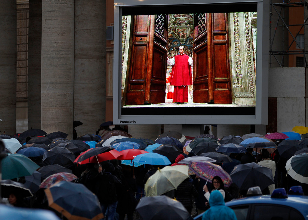 ". People watch on a video monitor in St. Peter\'s Square as Monsignor Guido Marini, master of liturgical ceremonies, closes the double doors to the Sistine Chapel in Vatican City Tuesday, March 12, 2013, at the start of the conclave of cardinals to elect the next pope. Marini closed the doors after shouting ""Extra omnes,\"" Latin for \""all out,\"" telling everyone but those taking part in the conclave to leave the frescoed hall. He then locked it. (AP Photo/Michael Sohn)"