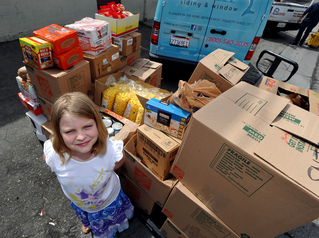 Description of . Halli Brainard, 9, of Whittier, stands with the food that she collected and donated to the Interfaith Food Center in South Whittier on Monday March 25, 2013. Brainard has been collecting money and food over the last three weeks and donated an extimated 1,200-pound of foons.