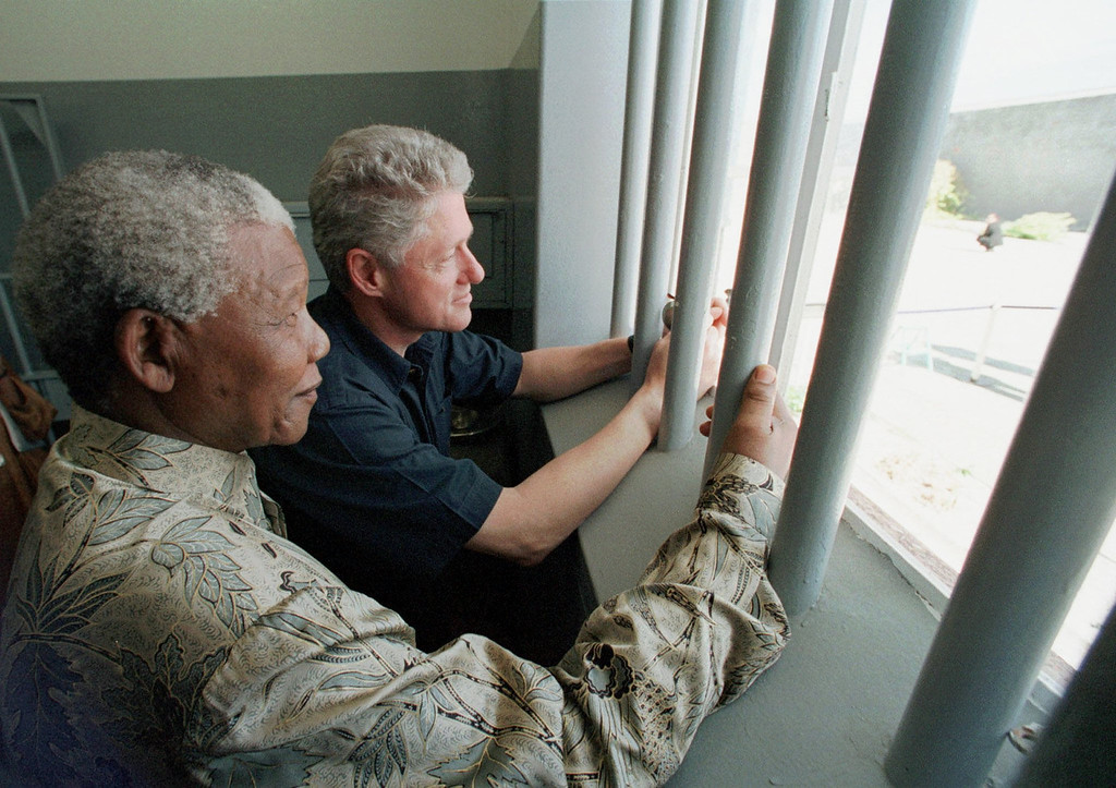 . South African President Nelson Mandela, foreground, and U.S. President Bill Clinton peer out from Section B, prison cell No. 5, on Robben Island, South Africa Friday, March 27, 1998. Mandela spent 18 years of his 27-year prison term on the island. Mandela Friday praised Clinton for his  correct instincts  on international matters and told South Africans who criticize his own ties to Cuba and Libya to  go and throw themselves into a pool.  (AP Photo/J. Scott Applewhite, Pool)