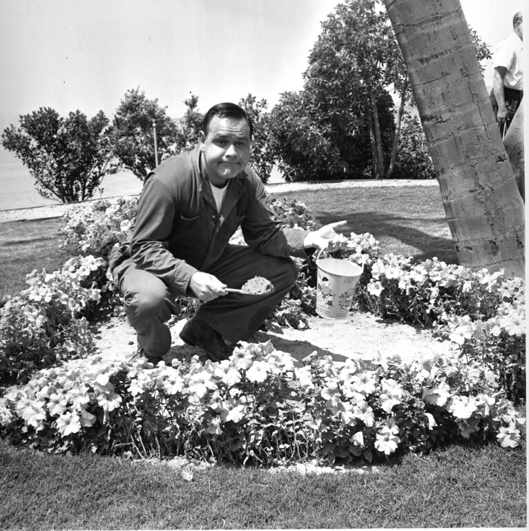 ". Comedian and actor Jonathan Winters holds a sand pail in a flower bed on the set of the movie ""It\'s a Mad, Mad, Mad, Mad World\"" in Hollywood, Ca., on Aug. 2, 1962.  (AP Photo)"