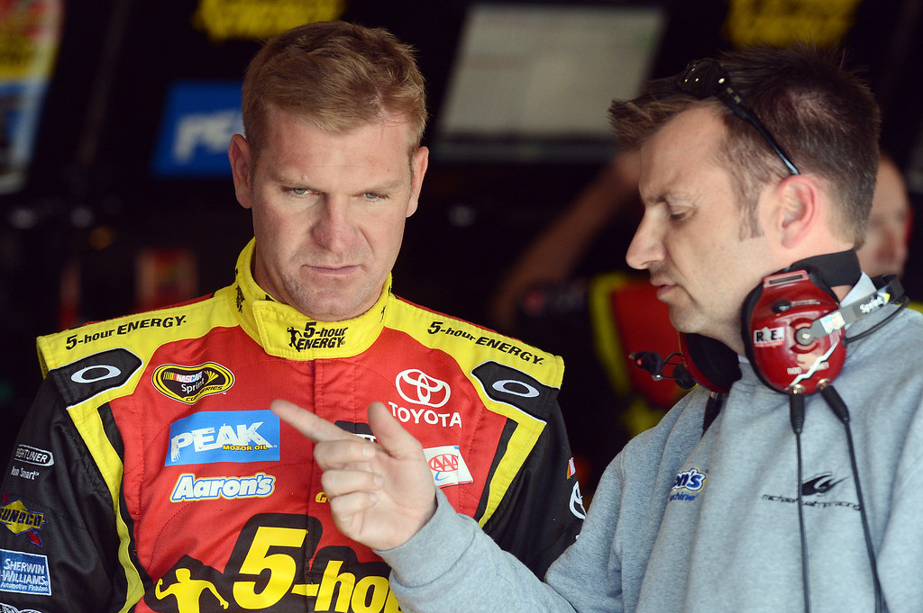 . (Will Lester/Staff Photographer) NASCAR driver Clint Bowyer talks with a crew member as he waits in the garage for his car to be prepared during the opening practice session for Sunday\'s Auto Club 400 Friday March 22, 2013.
