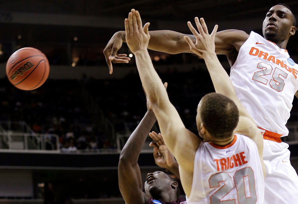 . Syracuse forward Rakeem Christmas (25) blocks a shot by Montana guard Will Cherry, bottom, as Syracuse\'s Brandon Triche (20) defends during the first half of a second-round game in the NCAA college basketball tournament in San Jose, Calif., Thursday, March 21, 2013. (AP Photo/Jeff Chiu)