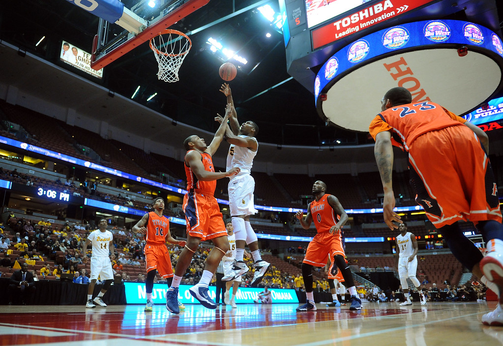 . LBSU\'s Mike Caffey shoots over Fullerton\'s Steve McClellan at the Honda Center in Anaheim, CA on Thursday, March 13, 2014. Long Beach State vs CSU Fullerton in the Big West men\'s basketball tournament. 1st half. LBSU won 66-56.  Photo by Scott Varley, Daily Breeze)
