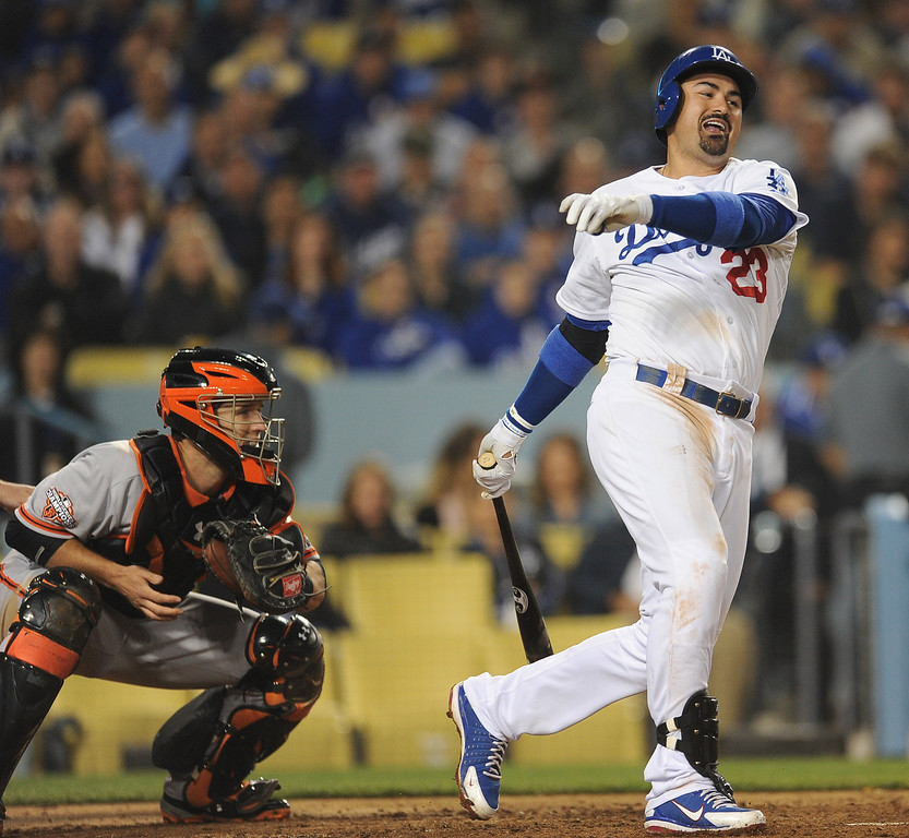 . Los Angeles Dodgers\' Adrian Gonzalez strikes out swinging with runners on as San Francisco Giants catcher Buster Posey looks on to end the sixth inning of their baseball game on Wednesday, April 3, 2013 in Los Angeles. 