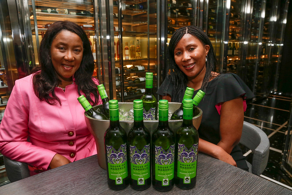. In this image taken on Thursday, Feb. 21, 2013, former South African president Nelson Mandela\'s daughter, Makaziwe Mandela, left, and his granddaughter Tukwini Mandela pose with some of their House of Mandela wines, in Bal Harbour, Fla. For decades, Nelson Mandela\'s name has been synonymous with freedom and political reform. Now with the launch of House of Mandela Wines, his daughter and granddaughter hope to add fine wine to the list of associations. (AP Photo/Wilfredo Lee)