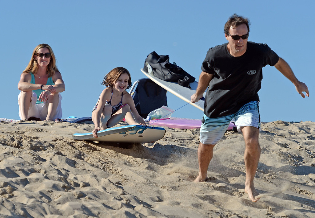 . Brian Malone gives his daughter Madie, 8, a ride on a boogie board, as, mom Ali watches, down a sand berm on the beach near the Hermosa Beach pier. The day after Christmas seemed more like the Fourth of July as people flocked to the beach Thursday, December 26, 2013, in Hermosa Beach, CA.  Photo by Steve McCrank/DailyBreeze