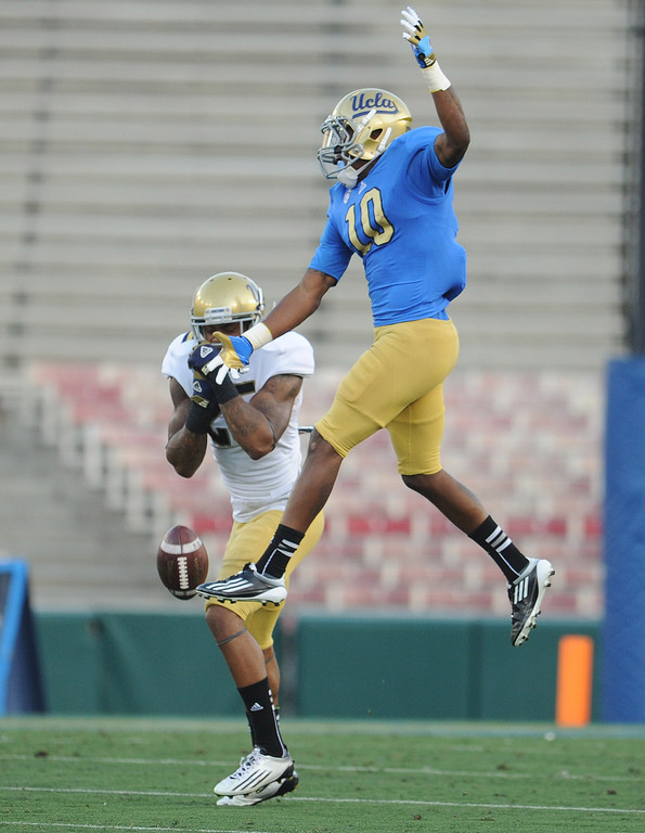 Description of . UCLA linebacker Brandon Sermons (25) breaks-up a pass to UCLA's Kenneth Walker (10) during the football spring showcase college football game in the Rose Bowl on Saturday, April 27, 2013 in Pasadena, Calif.    (Keith Birmingham Pasadena Star-News)