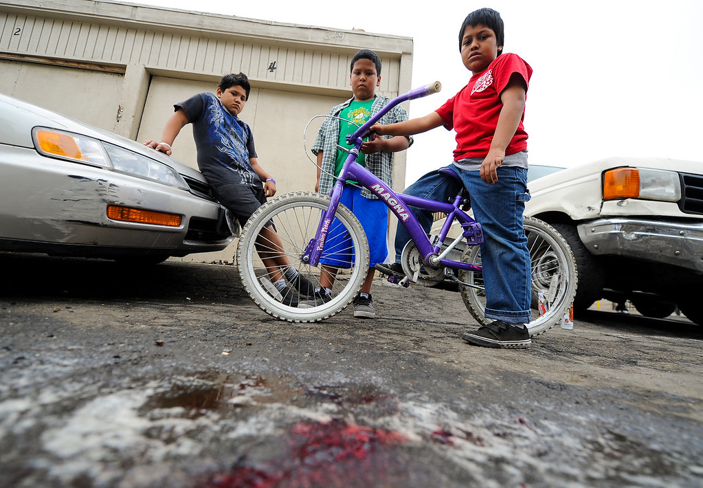 . Neighborhood children Jose Ruiz, 11, right, Anthony Verdugo, 10, and Christopher Lopez, 11, left, stare at a puddle of blood left behind from a fatal teenage victim as police investigate the scene of a double homicide on the 300 block of Orchid Lane in Pomonaon Saturday, April 13, 2013. Two teenagers, a 16-year-old and 13-year-old boy, were fatally shot and one adult male was critically wounded, according to authorities. (Rachel Luna / Staff Photographer)