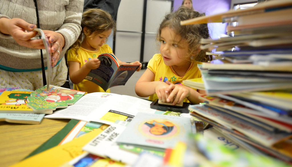. 03-16-2013--(LANG Staff Photo by Sean Hiller)- Volunteers and students the help Anderson Elementary School Library sort and process new and donated books as well as spiff up campus with some colorful murals at Saturday\'s event organized by Access Books. Brianna Gonzalez,4, right, helps stamp books as her twin Cianna, left, reads one of the donated books they are helping process.